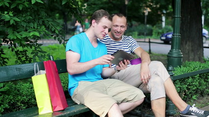 Young friends with tablet computer in the park