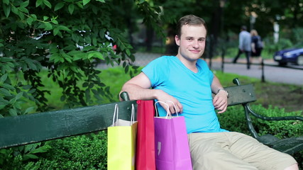 Happy man with shopping bags in the park