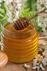 Acacia honey jar with a dipper and Acacia tree blossoms
