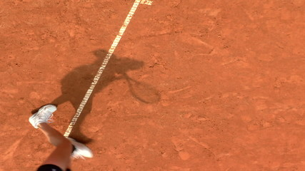 Shadow of a tennis player during serve motion in a clay court