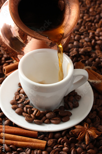 Cup and pot of coffee on coffee beans background