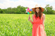 Portrait of beautiful young woman with pinwheel in the field