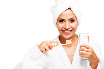 young woman in bathrobe brushing teeth