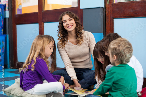 Teacher With Children Reading Book In Classroom