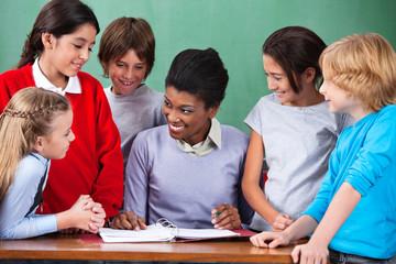 Happy Teacher Teaching Children At Desk In Classroom