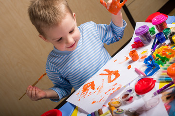 Cute smiling little boy painting at the table