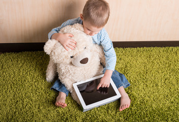 Boy and teddy bear with tablet computer, Top view