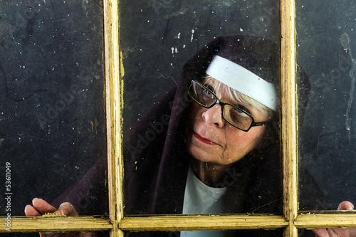 nun looking through a window