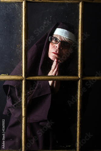 Nun praying through a window