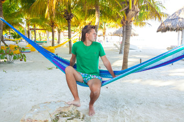 Young man sitting in hammock on the beach and looking at the sea