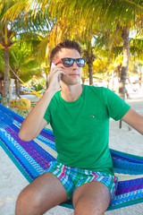 The young guy talking on the phone and relaxing in hammock on an
