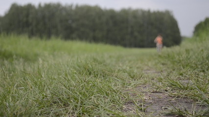 Woman in orange t-shirt with bicycle in summer field