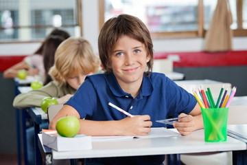Schoolboy Smiling While Sitting With Classmates In A Row At Desk
