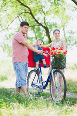 parents carry a child on a bicycle