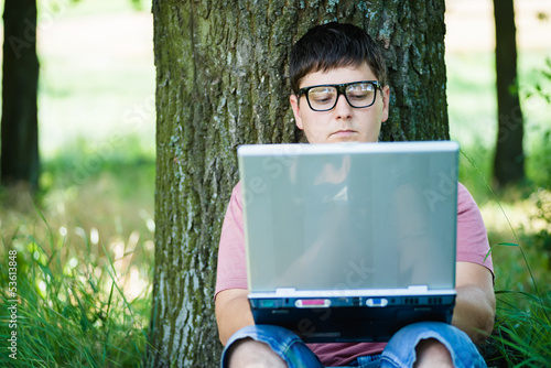 man in glasses using laptop on nature