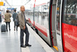Visually impaired man boarding a train at the station - 53614464
