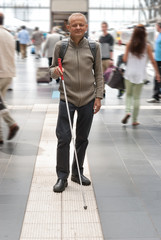 Blind man uses the tactile guidance system in the station
