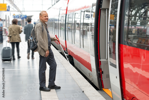 Visually impaired man boarding a train at the station