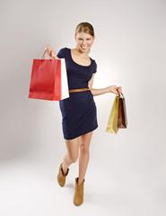 Lucky shopper. Beautiful blond woman holding shopping bags