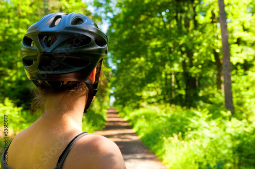 attractive female bicycle rider on a beautiful forest track