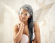 Young woman as angel with white wings over white obsolete wall