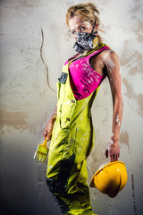 Female construction worker holding paint brush and hard hat