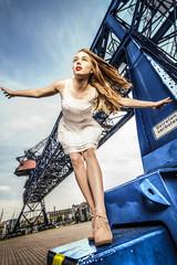 Frau im Sommerkleid vor Industriekulisse