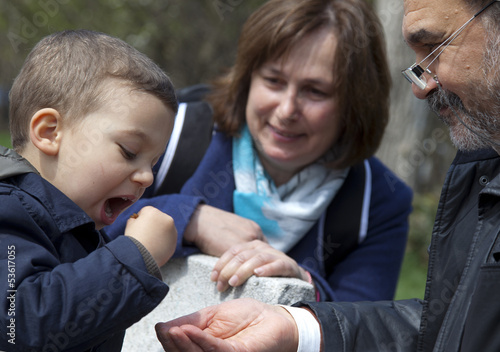 Grandparents feeding child park