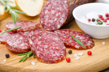 Italian salami sliced ​​into pieces on wooden cutting board