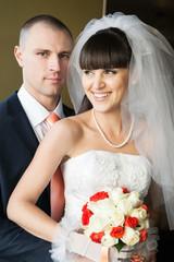 smiling bride looking away and groom