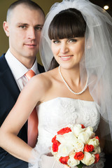 smiling bride holding bouquet of roses and groom