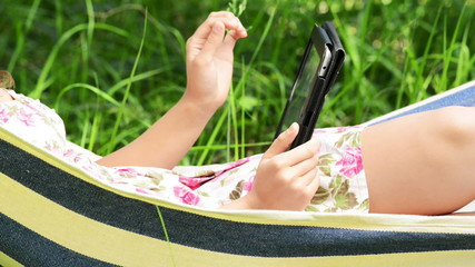 Young woman lying in a hammock in garden with E-Book on tablet c
