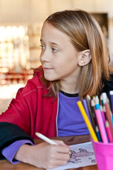 young girl colouring, looking away
