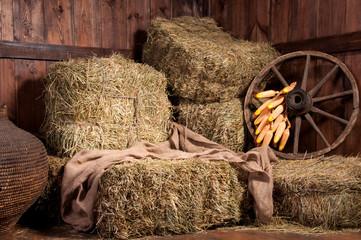 Interior of a rural farm - hay, wheel, corn.