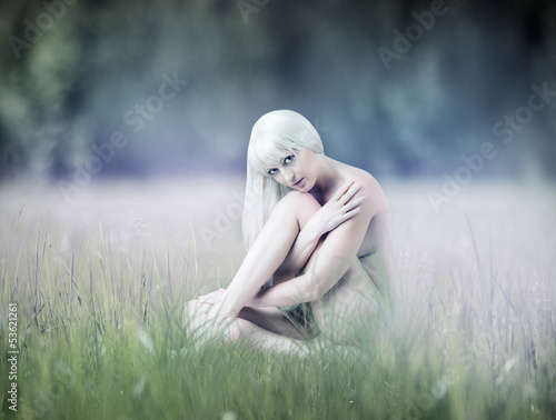 Young sexy woman sitting on meadow