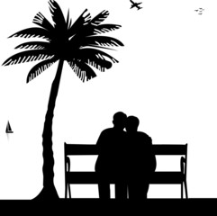 Lovely retired elderly couple sitting on bench on the beach