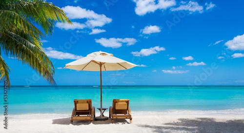 two deckchairs on the idyllic white beach in front of the turquo - 53623205