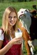 Junge Frau trinkt Milch vor der Kuh