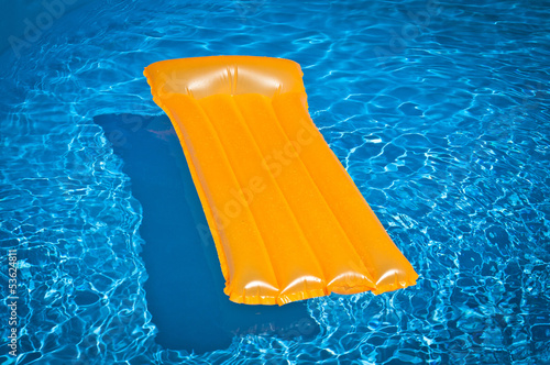 Inflatable mattress floating in a pool