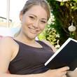 Junge Frau liest Roman im Garten
