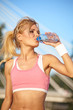 cheerful young attractive woman drinking water, outdoors