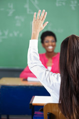 Teenage Girl Raising Hand At Desk