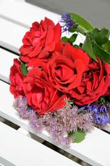 rote Rosen auf weißer Bank