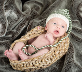 cute baby in a knit basket wearing a green and white knit hat