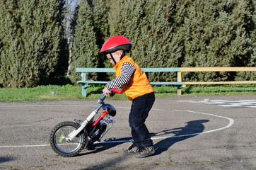 Little boy playing with his bike outdoors