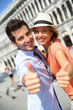 Cheerful couple showing thumbs up on San Marco Place