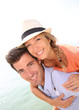 Man giving piggyback ride to beautiful blond girl with hat