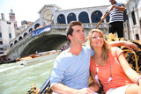 Couple on a Gondola ride passing by Rialto bridge, Venice