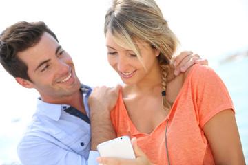 Portrait of sweet couple using smartphone