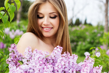 Sexy young woman with lilac flowers